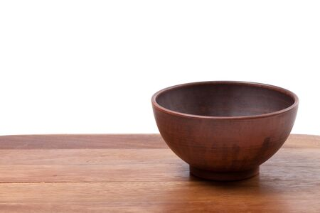 Empty ceramic bowl on wooden kitchen table  Isolated on white background  photo