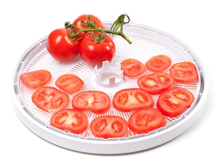 Fresh tomato prepared to dehydrated  On food dehydrator tray  photo