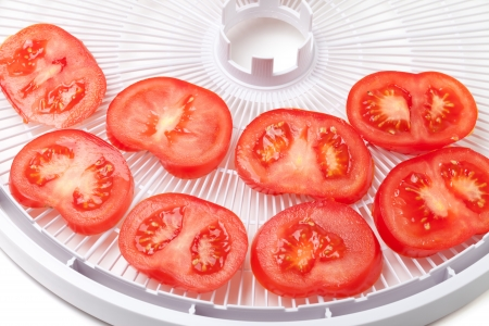 Fresh tomato on food dehydrator tray, ready to dry  Isolated on white background Stock Photo - 19019385