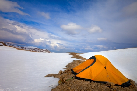 Orange tent in snow mountains. Turkey, Central Taurus Mountains, Aladaglar (Anti-Taurus), plateau Edigel (Yedi Goller) photo