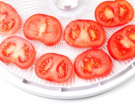 Ripe tomato on food dehydrator tray, ready to dry  On white background  photo