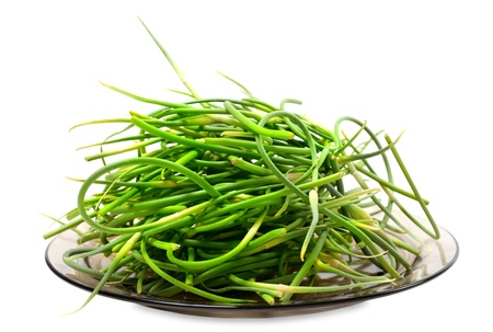 Fresh garlic scapes on plate. On white background. Stock Photo