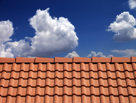 Roof tiles against blue sky with clouds Stock Photo