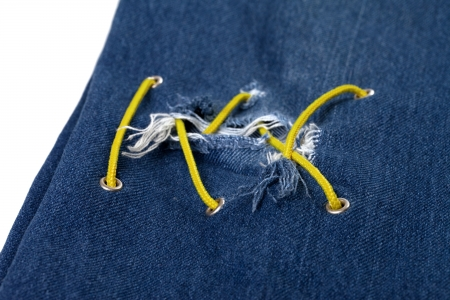 crisscross: Blue jean with hole and crisscross yellow lacing. Selective focus.