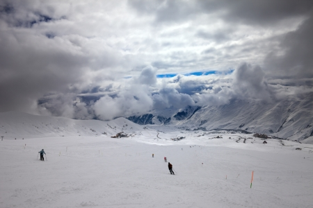 Skiers on ski slope before storm. Caucasus Mountains. Georgia, ski resort Gudauri. Wide angle view. photo