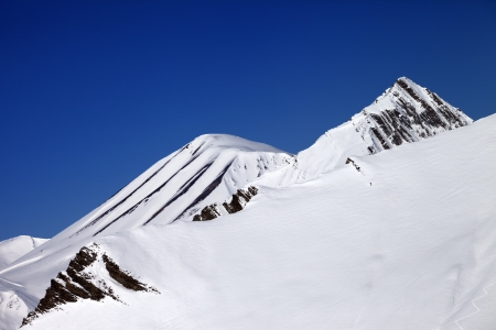 off piste: Off-piste slope and blue clear sky in nice day. Caucasus Mountains, Georgia, ski resort Gudauri. Stock Photo