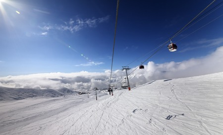 Gondola and chair lift in nice sunny day. Ski resort Gudauri, Georgia. Caucasus Mountains. Wide angle view. photo