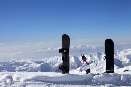 Three snowboards in snow near off-piste slope in sun day. Caucasus Mountains, Georgia, ski resort Gudauri. photo