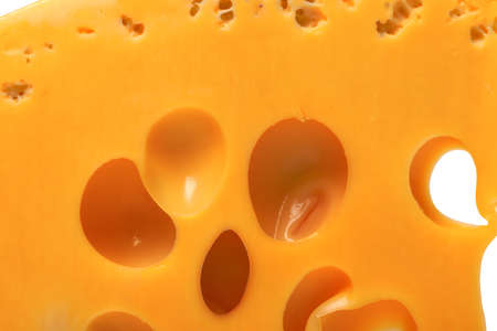 Slice of cheese with hole. Macro view. photo