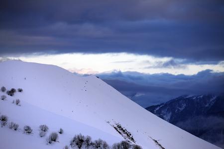 piste: Off-piste slope and cloudy sky at sunset. Caucasus Mountains, Georgia. Ski resort Gudauri.