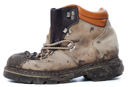Old dirty hiking boot isolated on white background