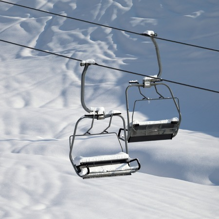 Two chair-lift with snowdrift in sun morning. Close-up view. Caucasus Mountains, Georgia, ski resort Gudauri. photo