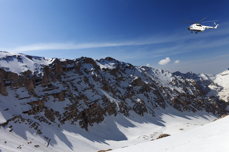 Helicopter in snowy sunny mountains at nice day photo