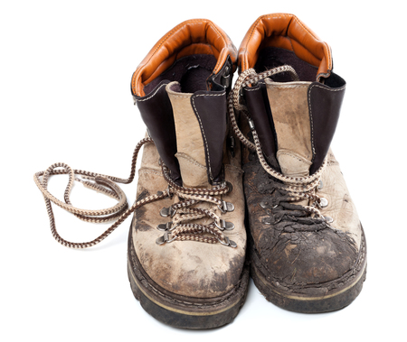 Pair of old dirty trekking boots isolated on white background photo