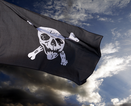 Jolly Roger (pirate flag) against storm clouds  photo