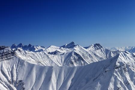 Snowy winter rocks in sun day, view from ski slope. Caucasus Mountains, Georgia, ski resort Gudauri. Stock Photo