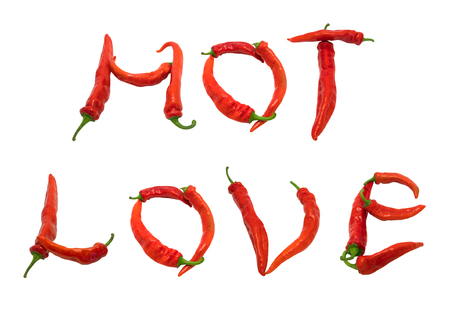 HOT LOVE text composed of red chili peppers. Isolated on white . photo