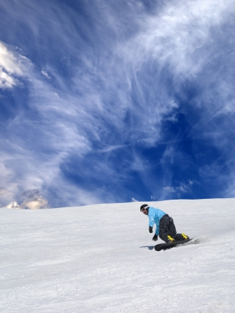 Snowboarder on off-piste slope and sky with clouds