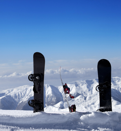 Three snowboards in snow near off piste slope in sun day. Caucasus Mountains, Georgia, ski resort Gudauri. photo