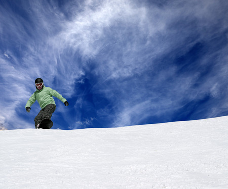 offpiste: Snowboarder on off-piste slope and blue sky with clouds