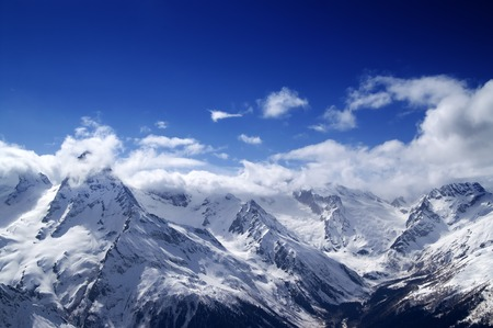 capped: Snowy mountains at sun day. Caucasus Mountains. View from ski resort Dombay. Stock Photo