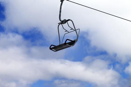Chair-lift and blue sky with clouds. Caucasus Mountains, Georgia, ski resort Gudauri. photo