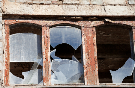 Wooden wall of old destroyed house with broken windows photo