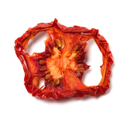 Dried slice of tomato. Isolated on white background. Close-up view. photo