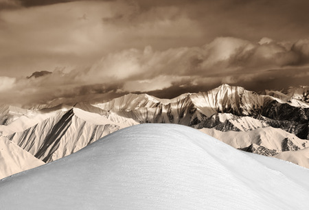 offpiste: Top of off-piste snowy slope and sepia mountains. Caucasus Mountains, Georgia, ski resort Gudauri.