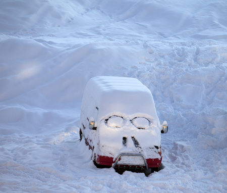 smiley face car: Snow-covered car with smiley in windshield. Ski resort at evening.