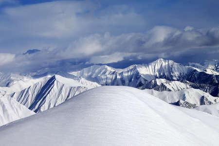 offpiste: Top of off-piste snowy slope and cloudy mountains. Caucasus Mountains, Georgia, ski resort Gudauri.