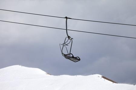 piste: Chair lift and off-piste slope at gray day. Caucasus Mountains, Georgia, ski resort Gudauri.