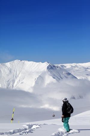 piste: Snowboarder on off-piste slope with new fallen snow at nice day. Caucasus Mountains, Georgia, ski resort Gudauri.