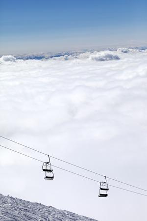 Ski slope, chair-lift and mountains under clouds. Caucasus Mountains, Georgia. Ski resort  Gudauri. photo