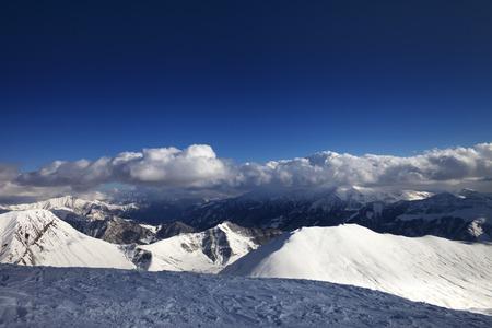 offpiste: Off-piste slope and beautiful snowy mountains in evening. Caucasus Mountains, Georgia. Ski resort Gudauri.