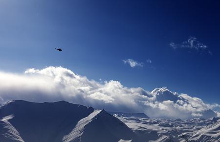 off piste: Helicopter above snowy plateau in evening. Ski resort Gudauri. Caucasus Mountains, Georgia.