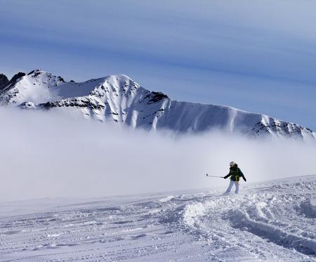 off piste: Snowboarder downhill on off-piste slope with newly fallen snow. Ski resort Gudauri. Caucasus Mountains, Georgia. Stock Photo