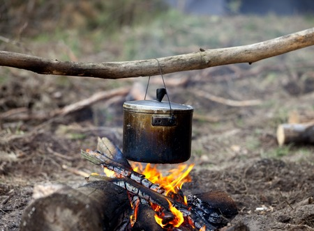 forest fire: Cooking in sooty cauldron on campfire at forest