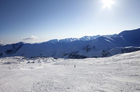ray trace: Skiers on ski slope. Caucasus Mountains, Georgia, ski resort Gudauri. Wide-angle view. Stock Photo