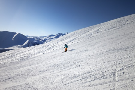 off piste: Skier on slope in sunny day. Caucasus Mountains, Georgia Stock Photo