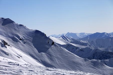 off piste: Off-piste slope and snowy mountains in morning. Georgia, ski resort Gudauri. Caucasus Mountains. Stock Photo