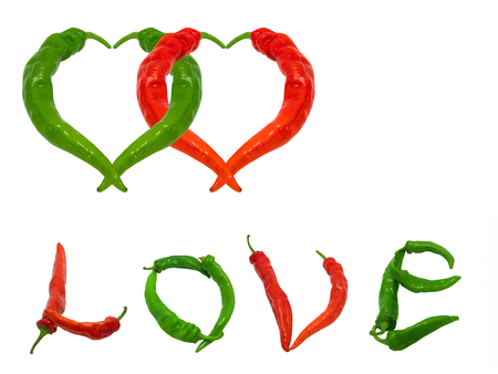 Two hearts and word Love composed of green and red chili peppers. Isolated on white background. photo