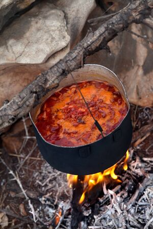 smut: Cooking borscht (Ukrainian traditional soup) on campfire. Stock Photo