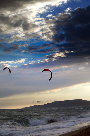 Two silhouette of power kites at beautiful sunset sky photo