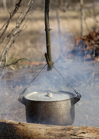 Cooking in sooty cauldron on campfire at spring forest photo