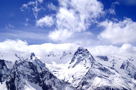 cusp: Snowy mountains in clouds at sun day. Caucasus Mountains, mount Belalakaya, ski resort Dombay. Stock Photo