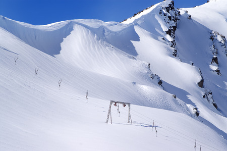 cornice: Old surface lift and mountains with snow cornice. Mount Cheget. Caucasus Mountains. Elbrus region. Stock Photo