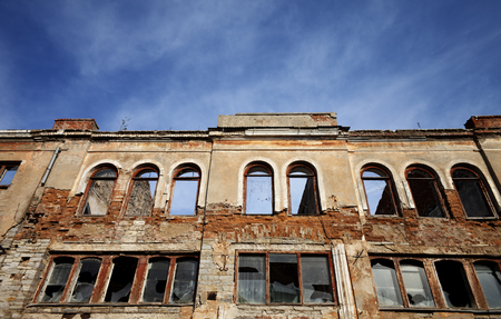 Facade of old destroyed house with broken windows. Wide angle view.