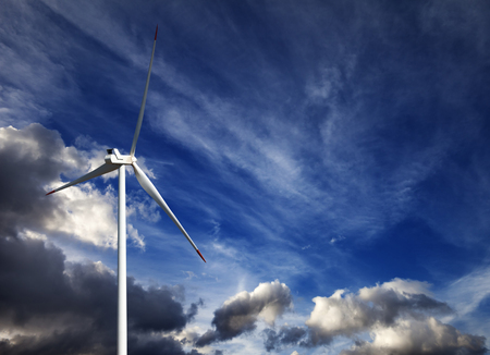 kinetic energy: Wind turbine and blue sky with storm clouds at summer day