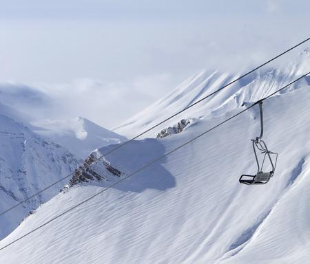 off piste: Chair lift and mountains in fog. Caucasus Mountains, Georgia, ski resort Gudauri.